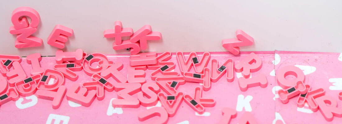 Pink scrambled letters against the wall