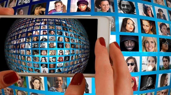 A smartphone taking a photo of a globe filled with faces