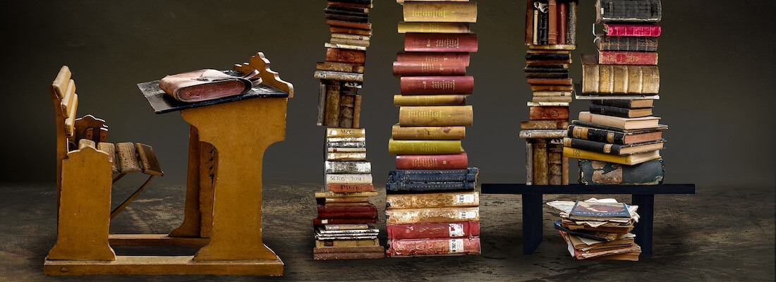 A collection of books, sitting next to a writing desk.