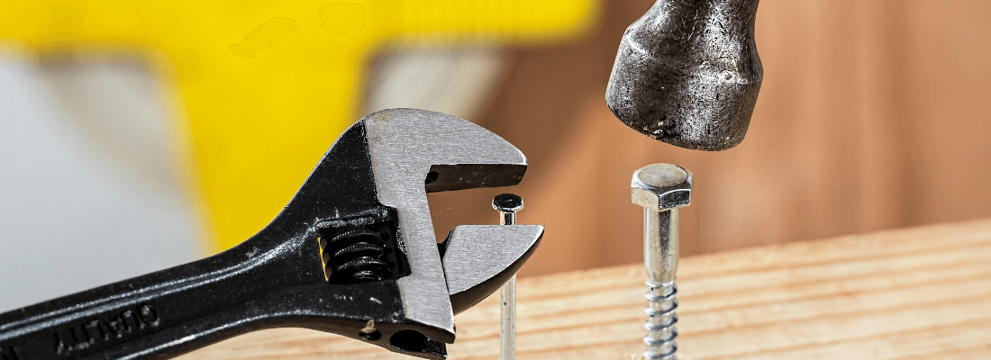 A hammer and spanner working on a nail and screw.
