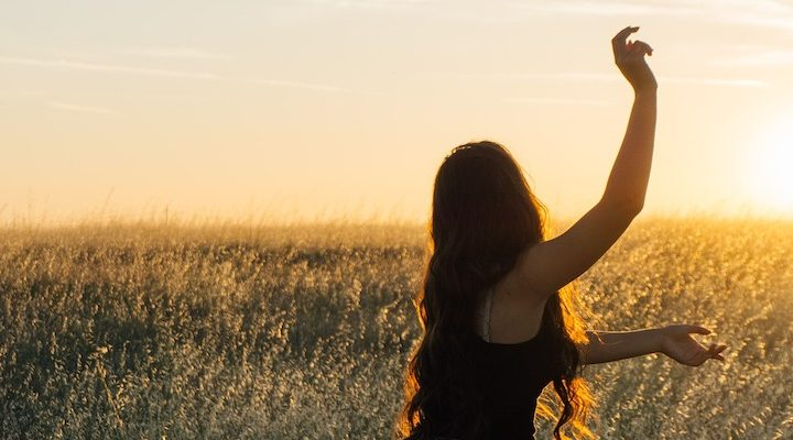 A woman running carefree in a field.