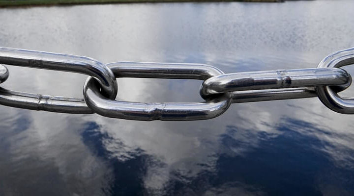 Chain links hanging in front of a lake.