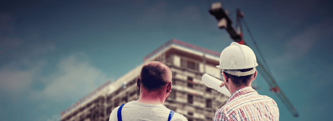 Men looking at a building that's under construction.